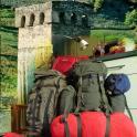 Spakowane plecaki na tle swańskiej wieży [grafika Adam Bińkowski]